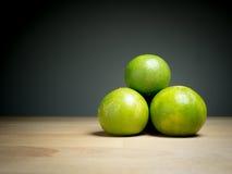 Övre gröna citroner för slut på trätabellen Arkivbild