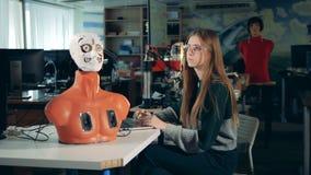 Övre - halva av en cyborgs kropp och unga kvinna som fungerar en bärbar dator stock video