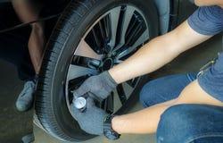 Övre hand för slut som kontrollerar luft in i ett bilgummihjul royaltyfria bilder