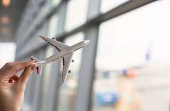 Övre hand för slut som rymmer en flygplanmodell Arkivfoto