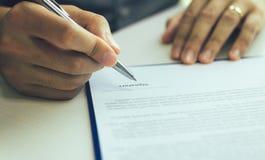 Övre handman för slut som undertecknar pappers- avtalsöverenskommelse för köpande hus arkivfoto
