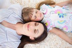 Övre sikt av modern och dottern som ligger på golvet Fotografering för Bildbyråer