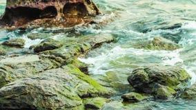Övre sikt för slut av den flödande klara vatten och vågen runt om stenen av flodsäng stock video