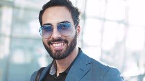Övre sikt för slut av den stiliga mannen av det östliga utseendet i solglasögon och den stilfulla dräkten som rakt till ser kamer stock video