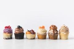 Övre sikt för slut av olika söta muffin på kakaställning Royaltyfri Foto