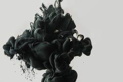 Övre sikt för slut av svart målarfärgfärgstänk i vatten som isoleras på grå färger arkivfoton