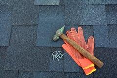 Övre sikt för slut på Asphalt Roofing Shingles Background Taksinglar - taklägga Asphalt Roofing Shingles Hammer handskar och spik Arkivfoto