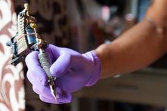 Övre tatueringhand och maskin för slut Royaltyfri Foto