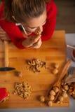 Övresiktshemmafru som tar tuggan av valnöten, medan laga mat Arkivbilder