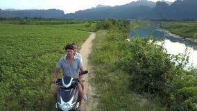 Övresiktsparet rider längs spår förbi floden på jordbruksmark lager videofilmer