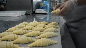 Última preparação antes de cozer Os croissant de vitrificação do padeiro com a lavagem do ovo que trabalha em sua cozinha, fazem  Fotos de Stock