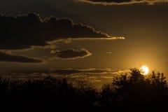 Última puesta del sol brillante anaranjada en el campo Foto de archivo