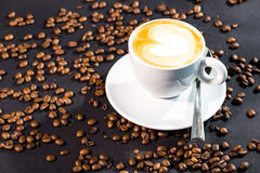 Últimas taza y habas del café en un fondo negro Imágenes de archivo libres de regalías