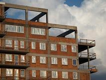 Últimos pisos de un bloque nuevamente construido de la vivienda del ladrillo rojo con las ventanas plásticas cubiertas con la hoj foto de archivo libre de regalías