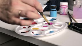 Úmidos fêmeas da mão a escova na paleta azul da pintura ilustração stock