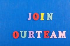 ÚNASE A NUESTRA palabra del EQUIPO en el fondo azul compuesto de letras de madera del ABC del bloque colorido del alfabeto, copie Imagenes de archivo