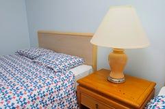Única cama com lâmpada Fotografia de Stock Royalty Free