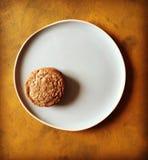 Única cookie na placa azul e no fundo textured amarelo Imagem de Stock