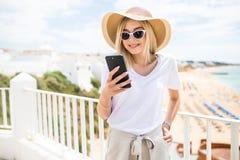 Única menina feliz que verifica um telefone esperto que senta-se em um terraço foto de stock