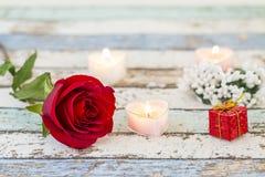 Única rosa vermelha, caixa de presente, velas, e flores brancas na tabela de turquesa fotografia de stock royalty free