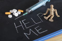 Única seringa, comprimidos e figura humana de madeira no quadro com ajuda mim Fotos de Stock