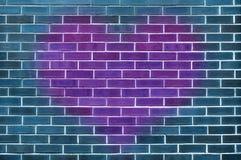 Único coração roxo grande em uma parede de tijolo azul Foto de Stock