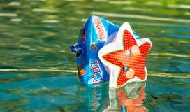 Único flutuador inflável do braço na água com reflexão foto de stock