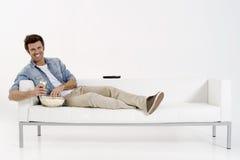 Único homem no sofá que presta atenção à tevê Fotografia de Stock Royalty Free
