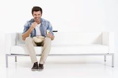 Único homem no sofá que presta atenção à tevê Fotografia de Stock
