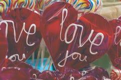 Único lollypop vermelho dos doces com texto branco eu te amo um lolly com trajeto de grampeamento Imagem de Stock Royalty Free