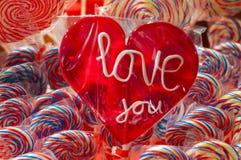 Único lollypop vermelho dos doces com texto branco eu te amo um lolly com trajeto de grampeamento Tenda com colorido e festivo tr Fotografia de Stock Royalty Free