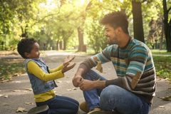 Único pai afro-americano que senta-se com sua filha na estrada imagem de stock royalty free