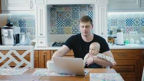 Único paizinho que trabalha em um laptop com bebê vídeos de arquivo