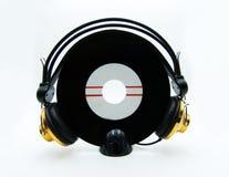 Único registro del vinilo con los auriculares de oro en el fondo blanco fotografía de archivo