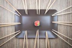 Único rolo de sushi na placa com os muitos dos hashis na tabela de madeira imagens de stock
