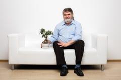Únicos anciões no sofá branco com um bonsai fotografia de stock royalty free