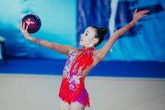 Únicos exercícios da ginasta do desempenho com bola Fotografia de Stock Royalty Free