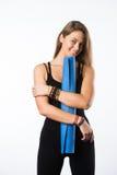 Üben Sie die Eignungfrau aus, die Holding-Yogamatte des Trainings zur stehenden betriebsbereit ist, die auf weißem Hintergrund ge Stockfotos