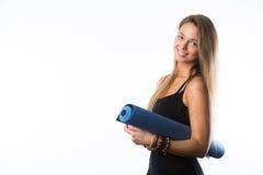Üben Sie die Eignungfrau aus, die Holding-Yogamatte des Trainings zur stehenden betriebsbereit ist, die auf weißem Hintergrund ge Lizenzfreies Stockfoto