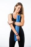 Üben Sie die Eignungfrau aus, die Holding-Yogamatte des Trainings zur stehenden betriebsbereit ist, die auf weißem Hintergrund ge Stockbild