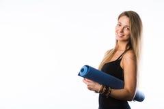 Üben Sie die Eignungfrau aus, die Holding-Yogamatte des Trainings zur stehenden betriebsbereit ist, die auf weißem Hintergrund ge Stockbilder