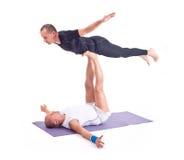 Übende Acro-Yogaübungen in der Gruppe/Vogel werfen auf Stockfotografie