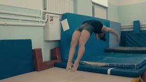 Übende Eignung des Mädchenathleten, an der Turnhalle, Salto zurück tuend stock video