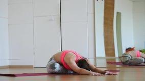 Übende junge Frau des Yoga der geeigneten Frau der Junge, die in der Turnhalle ausarbeitet stock footage