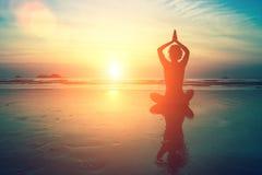 Übende Meditation der Frau nahe dem Ozean Stockfotos
