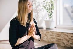 Übende Meditation der jungen Frau zuhause Stockbilder