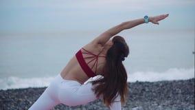 Übende Yogaaußenseite der aktiven Frau stock footage