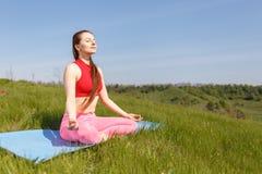 Übende Yogahaltungen der jungen Frau an im Freien Lizenzfreies Stockfoto