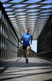 Übender laufender Sport des jungen athletischen Mannes, der städtische Stadtbrücke kreuzt Stockfoto