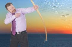 Übendes Bogenschießen des Geschäftsmannes auf Sonnenuntergang lizenzfreie stockbilder